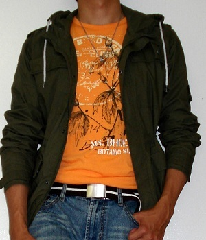 A Light Orange T Shirt Underneath A Dark Green Jacket