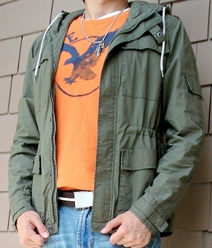 Wearing a dark green jacket and an orange graphic tee