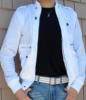 White perforated jacket with a black t-shirt inside and a pair of light blue jeans